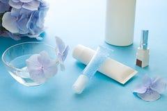 Os cosméticos orgânicos azuis fecham-se acima com flores e tubos da hortênsia com gel e creme fotos de stock royalty free