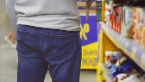 Os couros crus cleptomaníacos do homem o chocolate roubado no bolso traseiro das calças de brim video estoque