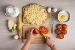 Os cozinheiros chefe das mãos cortaram os tomates, cozinhando ingredientes da pizza em vagabundos de madeira Fotografia de Stock Royalty Free