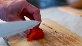 Os cozinheiros chefe das mãos dos homens cortaram um tomate na placa de madeira Preparação da salada vegetal vídeos de arquivo