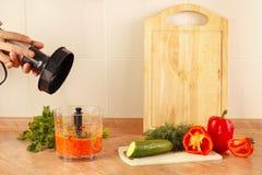 Os cozinheiros chefe das mãos estão indo aos vegetais do fragmento no misturador Imagens de Stock