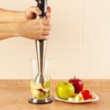 Os cozinheiros chefe das mãos estão indo misturar o cocktail de fruto no misturador imagem de stock royalty free