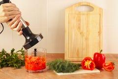 Os cozinheiros chefe das mãos estão indo misturar a pimenta vermelha e o tomate no misturador imagens de stock royalty free