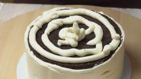 Os cozinheiros chefe de pastelaria nivelam o creme com uma espátula da cozinha filme