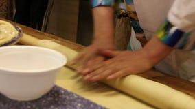 Os cozinheiros chefe masculinos entregam a preparação da massa com pino do rolo video estoque