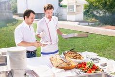 Os cozinheiros novos estão servindo o alimento no bufete no evento Fotos de Stock