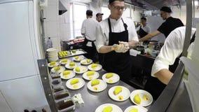 Os cozinheiros que trabalham na cozinha no restaurante video estoque
