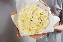 Os cravos amarelos macios florescem nas mãos do papel de embalagem do florista Foto de Stock
