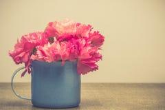 Os cravos cor-de-rosa brilhantes florescem no copo azul na tabela Imag de Vintge Imagens de Stock Royalty Free