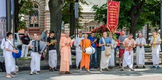 Os crentes da sociedade para Krishna Consciousness no centro de Lviv em Ucrânia, perto do teatro da ópera jogam cilindros, harmôn imagem de stock