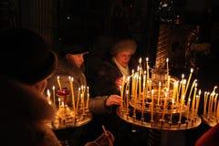 Os crentes ortodoxos iluminam velas em Pskov, Rússia Fotografia de Stock Royalty Free