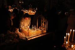 Os crentes ortodoxos iluminam velas em Pskov, Rússia Imagem de Stock Royalty Free