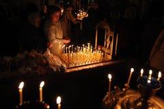Os crentes ortodoxos iluminam velas em Pskov, Rússia Imagem de Stock