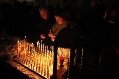 Os crentes ortodoxos iluminam velas em Pskov, Rússia Fotografia de Stock