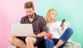 Os criadores satisfeitos dos pares trabalham com portátil e smartphone Profissão moderna A menina do homem cria a rede satisfeita foto de stock royalty free