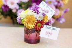 Os crisântemos florescem no vaso de vidro roxo com o cartão do feliz aniversario Fotografia de Stock Royalty Free