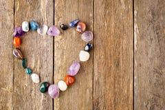 Os cristais curas caídos no coração dão forma no fundo de madeira Fotografia de Stock