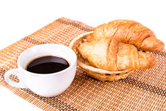 Os croissants franceses frescos e saborosos em uma cesta e em uma chávena de café seriram Imagem de Stock Royalty Free