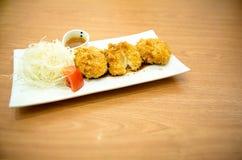 Os croquetes do queijo da batata, prato lateral são saque da couve e do tomate na placa branca fotografia de stock