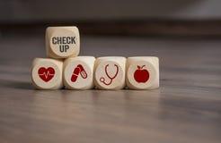 Os cubos cortam com verificação médica acima e ícones fotografia de stock