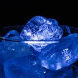 Os cubos de gelo azuis fecham-se acima em um vidro Imagens de Stock