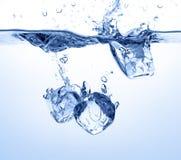 Os cubos de gelo deixaram cair na água Imagens de Stock