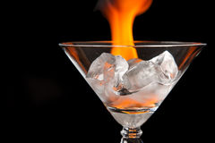 Os cubos de gelo no vidro com a chama no preto brilhante surgem Foto de Stock