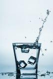 Os cubos de gelo que espirram no vidro, cubo de gelo deixaram cair no vidro da água, água fresca, fria, isolada no azul, backgrou Imagens de Stock