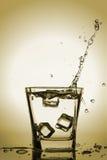 Os cubos de gelo que espirram no vidro, cubo de gelo deixaram cair no vidro da água Fotografia de Stock Royalty Free