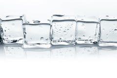 Os cubos de gelo transparentes com água deixam cair no fundo branco Fotografia de Stock