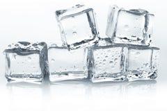 Os cubos de gelo transparentes com água deixam cair no fundo branco Imagens de Stock Royalty Free