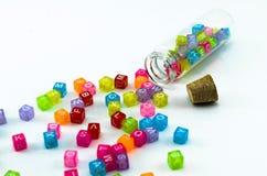 Os cubos pequenos coloridos isolados com caráteres dispersaram do tubo de ensaio no fundo branco Imagens de Stock Royalty Free