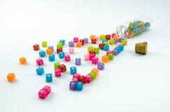 Os cubos pequenos coloridos isolados dispersaram no fundo branco Imagem de Stock
