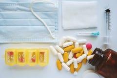Os cuidados médicos e os conceitos médicos incluem comprimidos, vitaminas, garrafa, caixa, seringa, agulha, gaze e máscara protet fotografia de stock royalty free