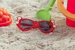 Os óculos de sol e os brinquedos das crianças encontram-se em uma praia na areia r Imagens de Stock Royalty Free