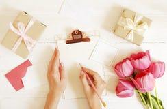 Os cumprimentos femininos da escrita da mulher da composição do desktop no cartão vazio cobrem a prancheta, ramalhete cor-de-rosa fotos de stock
