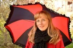 Os custos da jovem mulher sob um guarda-chuva preto-vermelho Fotografia de Stock Royalty Free