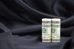 Os dólares americanos com fundo preto do cetim refletem o sophisticat Fotografia de Stock
