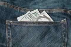Os dólares americanos e o preservativo nas calças de brim pocket Fotos de Stock Royalty Free