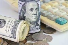 Os dólares americanos rolam o lugar nas moedas do dinheiro com calculadora Foto de Stock