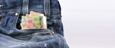 Os dólares canadenses do valor 20, 50 e 100 em calças de brim azuis da sarja de Nimes Pocket, conceito no dinheiro do salário, di Fotos de Stock Royalty Free