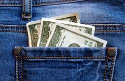 Os dólares do dinheiro encontram-se no bolso traseiro das calças de brim imagem de stock royalty free