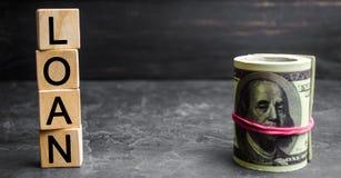 Os dólares e a inscrição do dinheiro no ` de madeira dos blocos emprestam o ` Interesse pagável Reembolso adiantado do empréstimo imagens de stock royalty free