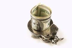 Os dólares e o aço algemam em um fundo branco Foto de Stock