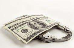 Os dólares e o aço algemam em um fundo branco Fotografia de Stock Royalty Free