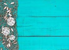 Os dólares e os shell de areia na rede dos peixes na praia de madeira azul da cerceta assinam Imagens de Stock Royalty Free