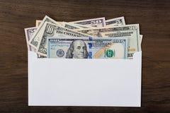 Os dólares no branco envolvem no fundo de madeira imagens de stock