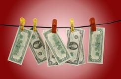 Os dólares penduram em uma corda Fotografia de Stock Royalty Free
