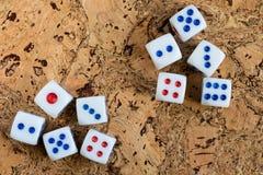 Os dados brancos jogados na tabela com uma cortiça marrom terminam Foto de Stock