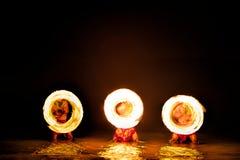 Os dançarinos do fogo criam os círculos do fogo que incandescem na água fotos de stock